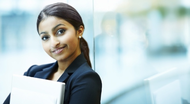 Human Resources and Payroll News: Portrait of a charming young business woman holding a laptop in her hand