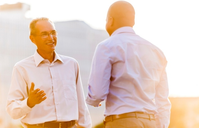 Smiling businessman talking to salesperson while standing outdoors