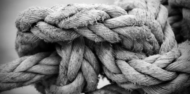 closeup of a knotted rope | Managing payroll can be like trying to untie an impossible knot